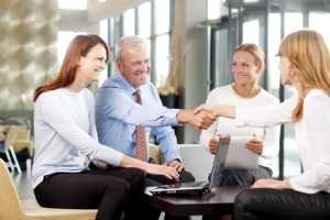 Old businessman shaking hands with confident business woman at meeting.